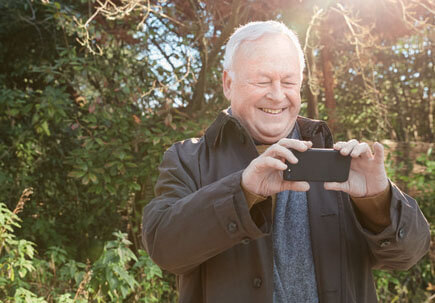 Man taking a photo on his phone in the countryside