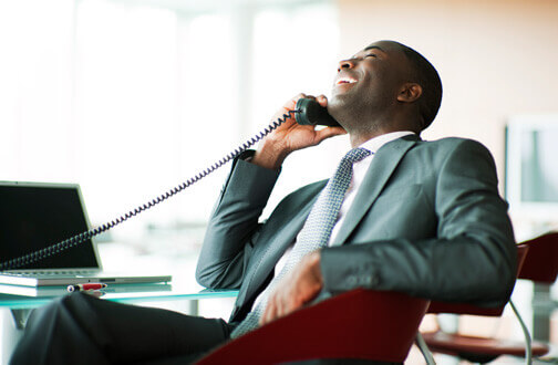 Man leaning back in his office chair whilst laughing on the phone