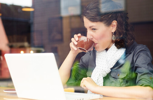 Woman in a cafe drinking coffee on her laptop